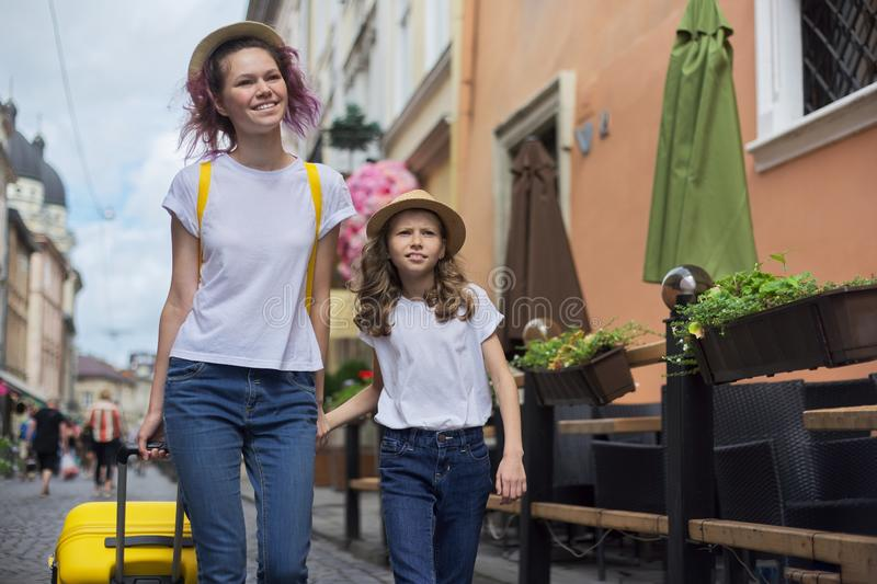 Two girls walking in tourist city holding hands with yellow suitcase royalty free stock photos