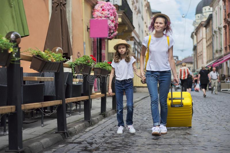 Two girls walking in tourist city holding hands with yellow suitcase royalty free stock photography