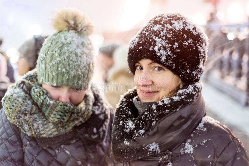 Two girls in warm winter clothes in heavy snow. Brightly visited city street. Snowflakes lie on their clothes and hats stock photography
