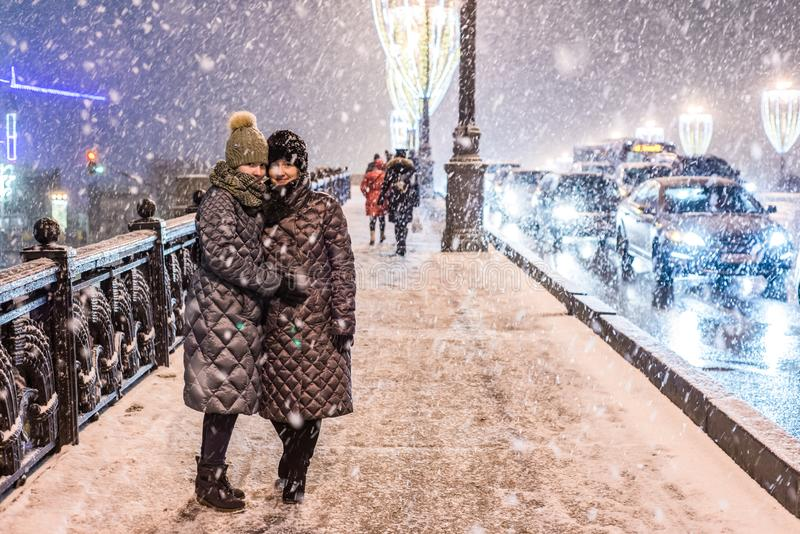 Two girls in warm winter clothes in heavy snow are standing on the illuminated sidewalk. Nearby are driving cars stock images