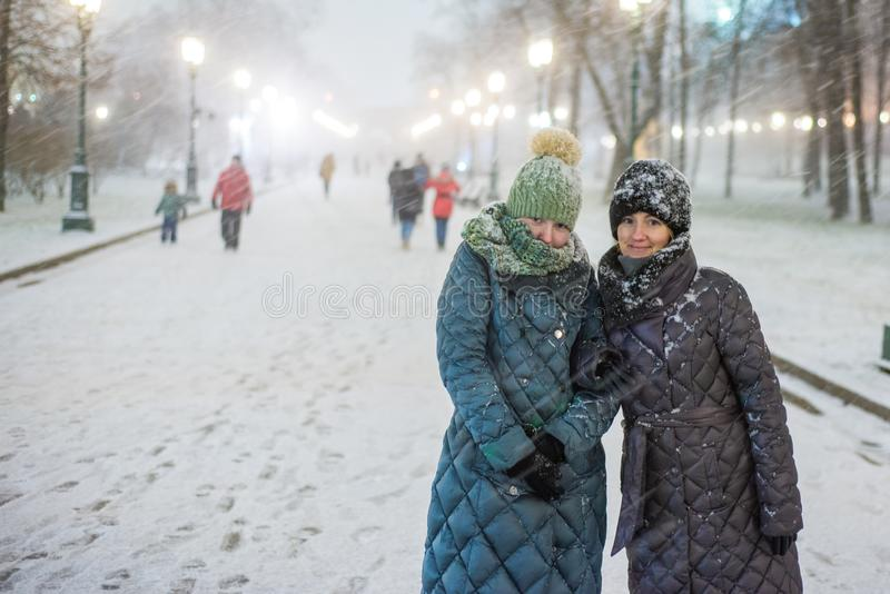 Two girls in warm winter clothes in heavy snow are standing on a lighted park alley. Snowflakes lie on their clothes royalty free stock photo
