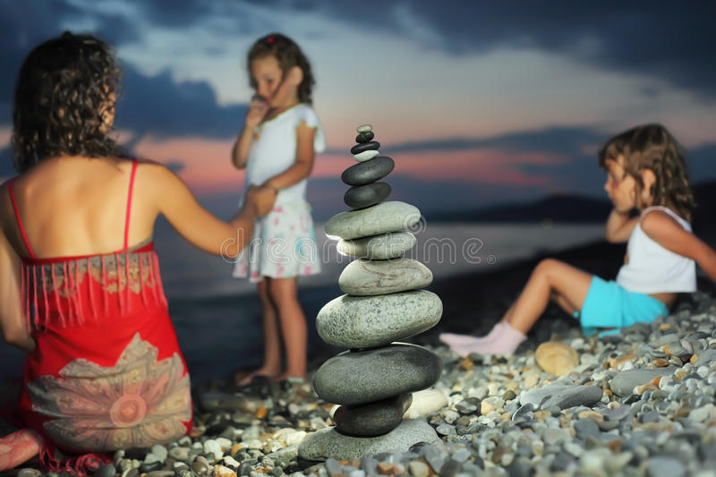 Download Two Girls And Woman Sitting On Stone Seacoast Stock Image - Image: 13021491
