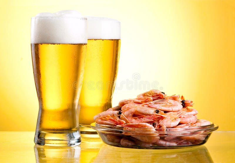 Two glass of beer and cooked shrimp stock images