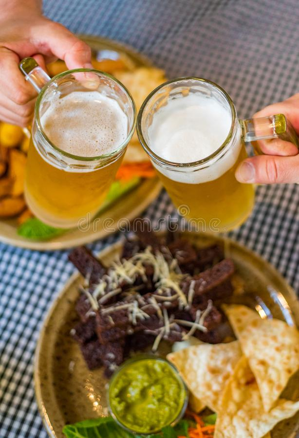 Two glass of beer in hand. Beer glasses clinking in bar or pub on table with food background. Close-up view of a two glass of beer in hand. Beer glasses clinking royalty free stock images