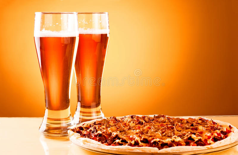 Two glass of beer and pizza stock photography