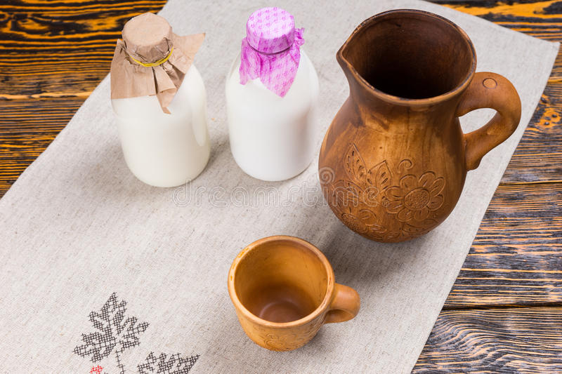 Two glass bottles of farm fresh creamy milk. With a pottery jug or pitcher and mug on a rustic table, high angle view stock images