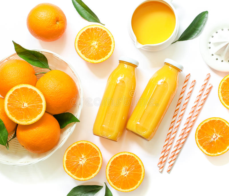 Two glass bottles of fresh orange juice, straws and oranges isolated on white background top view. Two glass bottles of fresh orange juice, straws and oranges stock image