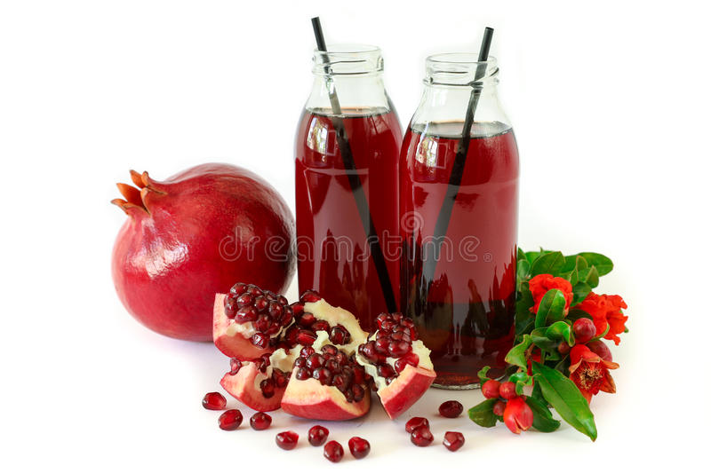 Two glass bottles of pomegranate juice, fruit, seeds and flowering branch of pomegranate tree isolated on white. stock photos