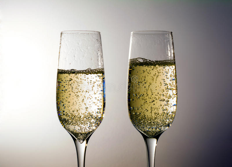 Two glass of champagne wine close up, bubbles, on grey background royalty free stock photos