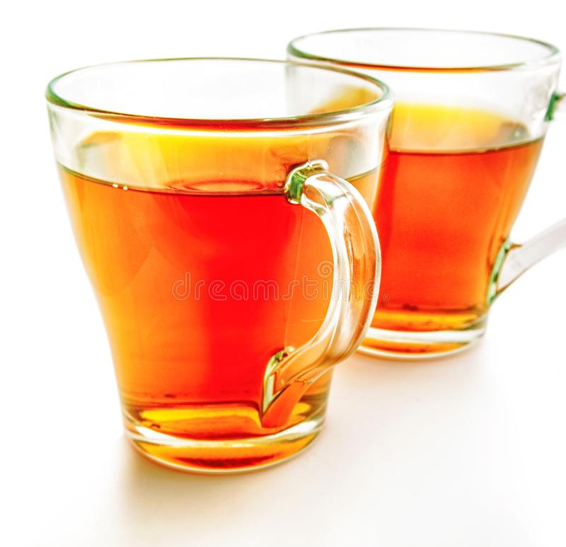 Two glass cups of tea on a white background stock photo