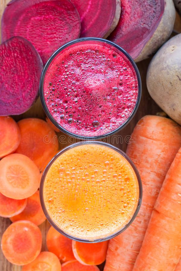 Two glass of fresh beet and carrot juice, beetroot and carrots vegetable, top view. stock photos
