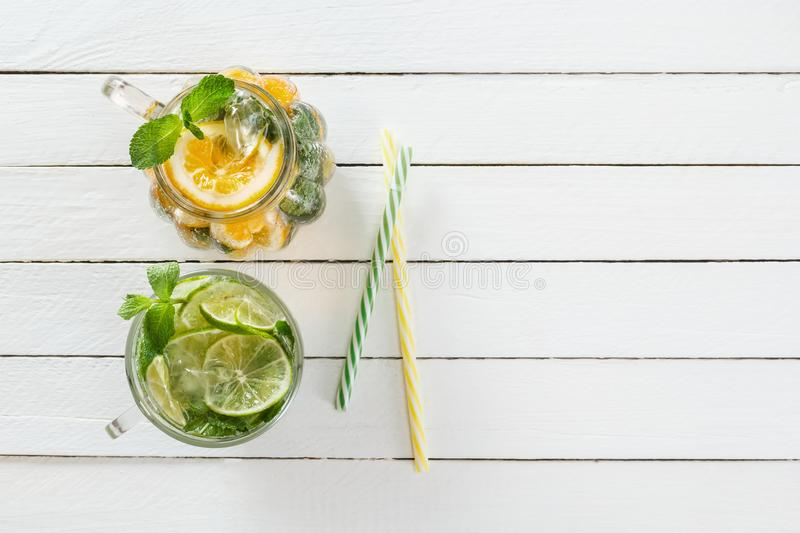 Two glass glasses with homemade lemonade from lime and lemon, cocktail tubes on a white wooden rustic background stock images