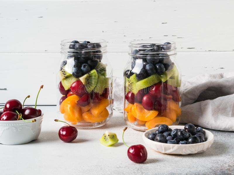 Two glass jars with berries and fruits. Fruit salad with apricots, kiwi, cherries and blueberries in glass jars on white royalty free stock images