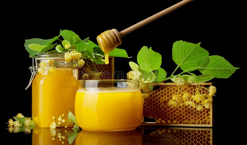 Two glass jars full of goldish honey, bee honeycombs and Linden flowers isolated on black stock images