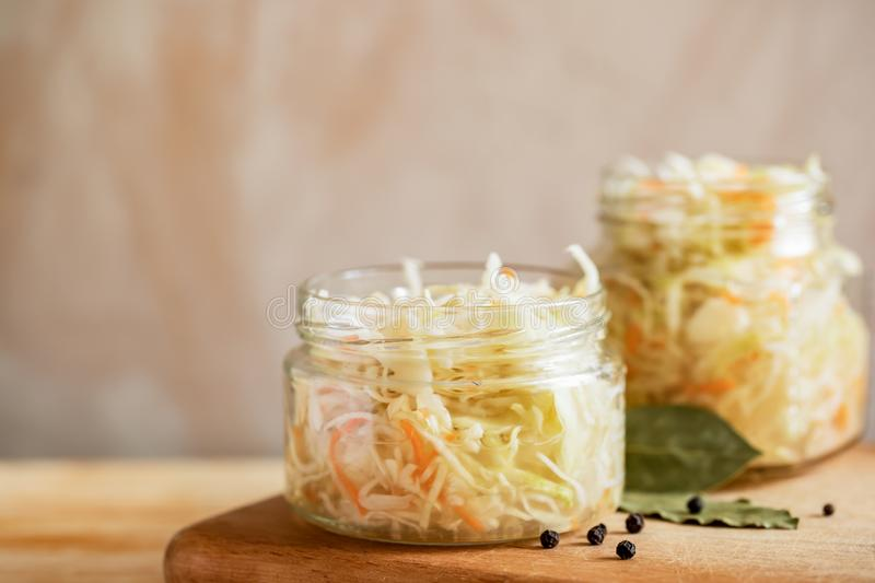 Two glass jars with sauerkraut are standing on wooden cooking board on light background with copy space. stock photos