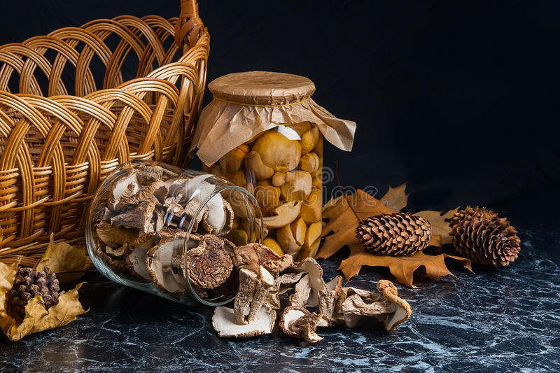Two glass jars with wild mushrooms on black marble background. One jar with dry mushrooms and one with pickled mushrooms. Several dry white wild mushrooms on stock images