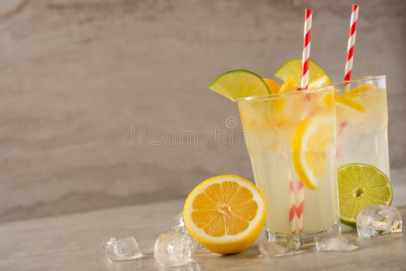 Two glass of lemonade with lemons and lime and straw, on a dark background, with space, a cool drink and summer mood.  royalty free stock image