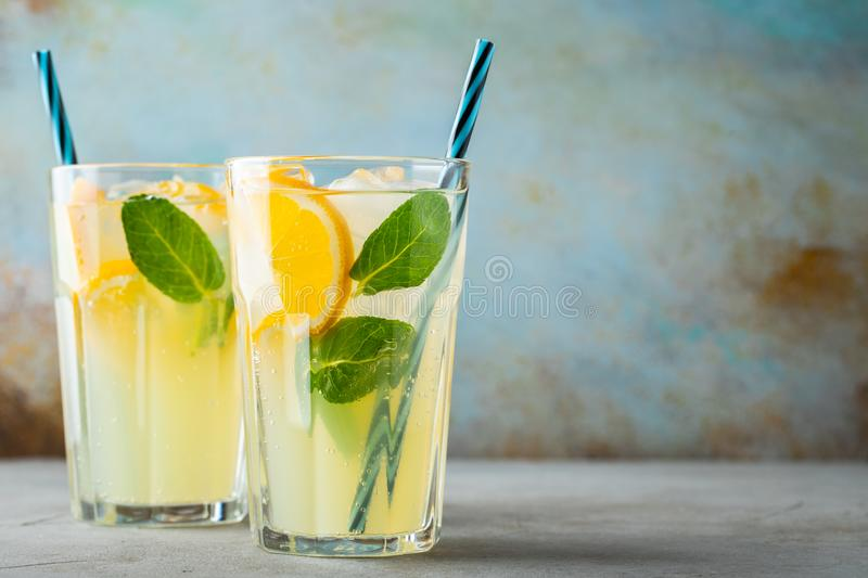 Two glass with lemonade or mojito cocktail with lemon and mint, cold refreshing drink or beverage with ice on rustic blue stock photo