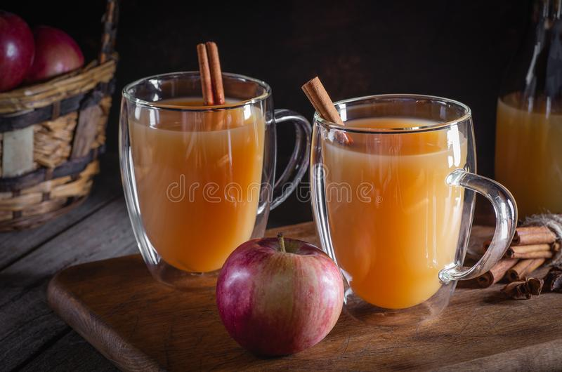 Glass Mugs of Apple Cider. Two glass mugs of apple cider with cinnamon sticks on a rustic wooden surface and dark background stock photo