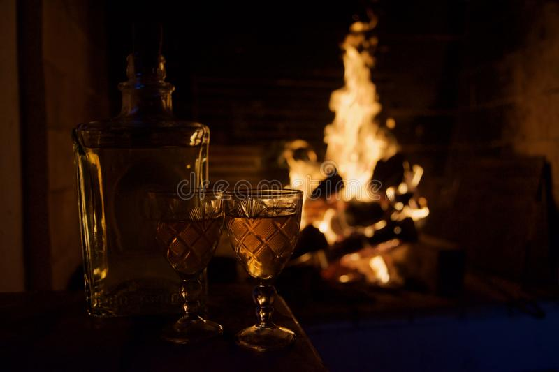 Two glass mugs of hot drink or alcoholic drink in front of warm fireplace. Magical relaxed cozy atmosphere near fire. Autumn or winter concept stock photography