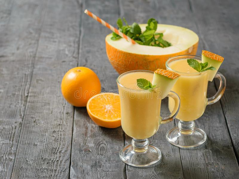 Two glass mugs with melon smoothie and a half melon with a cocktail tube on a black wooden table. Two glass mugs with melon smoothie and a half melon with a stock images