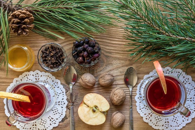 Two glass of mulled wine with cinnamon sticks, slice of oranges and apple, star anise on a wooden table royalty free stock photos