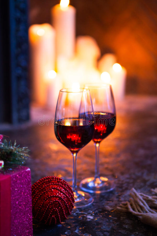 Two glass with red wine on Christmas tree and fireplace backgrou stock photo