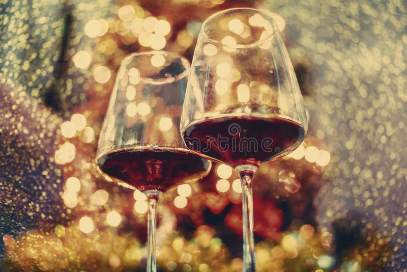 Two glass of red wine in front of christmas tree lights bokeh. New year eve and xmas celebration party stock photography