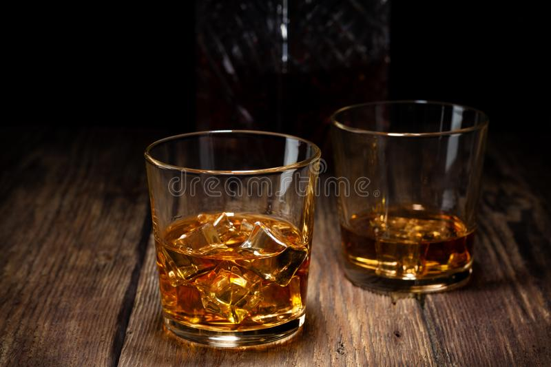 Two glass of whiskey with ice and crystal decanter. On wooden table stock photo