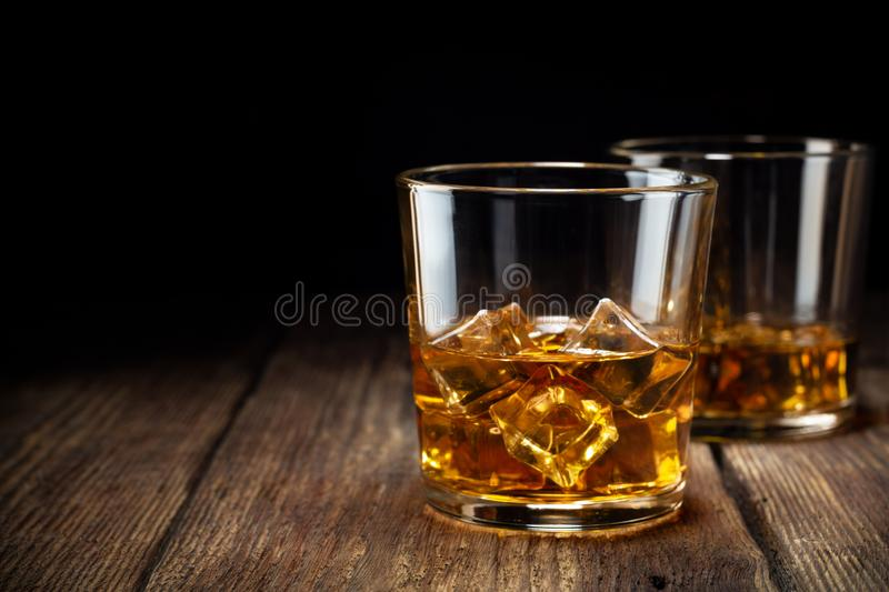 Two glass of whiskey with ice on wooden table stock photo