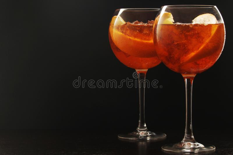Two glasses with aperol spritz cocktail. Two wine glasses with bright orange aperol sprtitz coctail at black background stock images