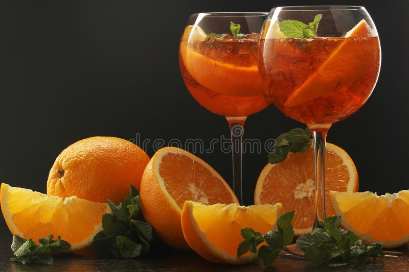 Two glasses with aperol spritz cocktail. Two wine glasses with bright orange aperol sprtitz coctail at black background stock photography