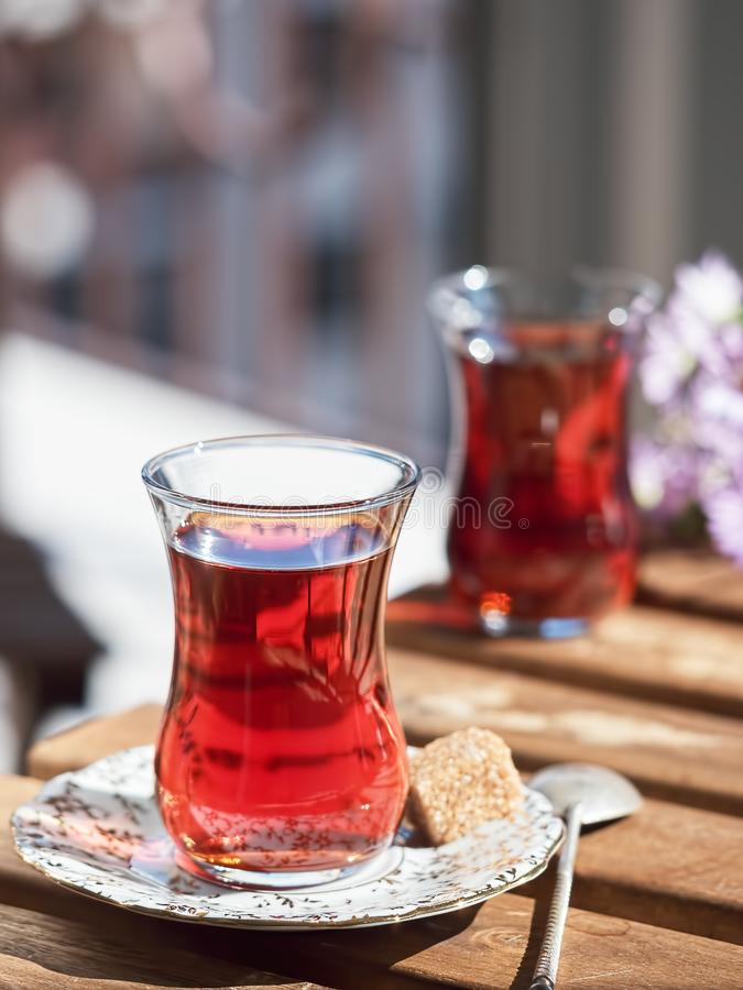 Two glasses of armudu tea on a saucer, located on a wooden table in the loggia. A piece of cane sugar and a spoon on a saucer. Bouquet of wildflowers in ukgu stock image