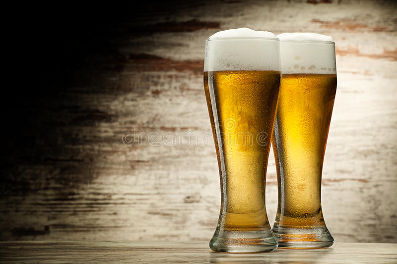 Two glasses of beer. Over vintage wood background royalty free stock photos