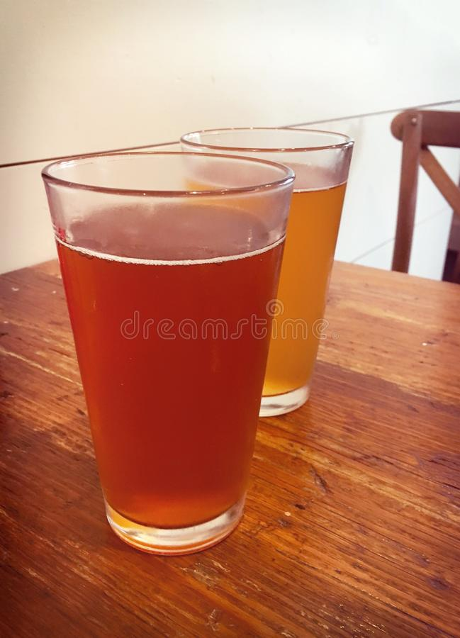 Two glasses of beer. A glass of amber ale and wheat beer on wood royalty free stock images