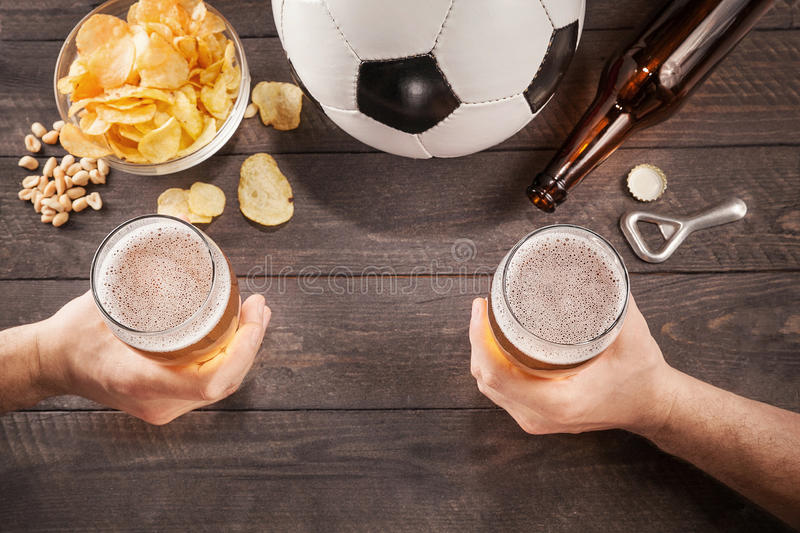 Two glasses of beer in men's hands. Chin-chin stock image
