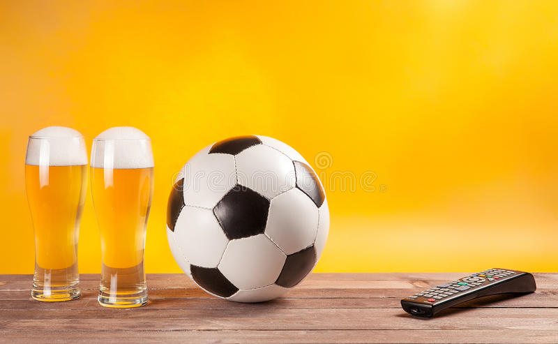 Two glasses beer and soccer ball near tv remote stock image