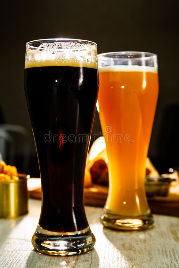 Two glasses of beer standing on the table on a dark background stock images