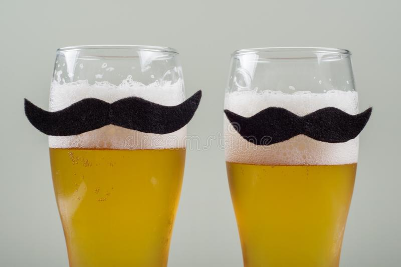 Two glasses with beer and symbolic mustache. Background grey wall stock photos