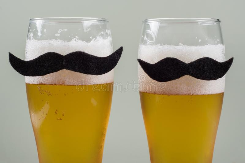 Two glasses with beer and a symbolic mustache. Background - olive wall stock photos