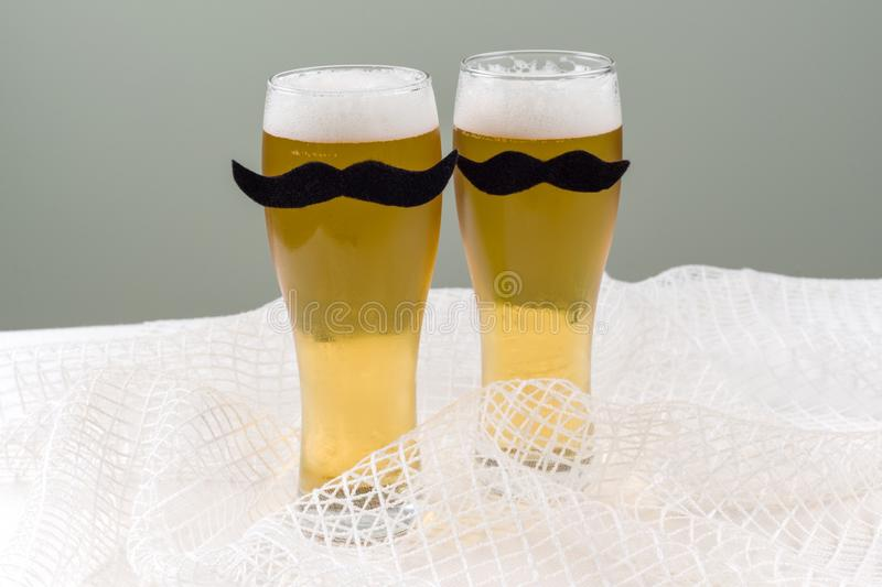 Two glasses with beer and a symbolic mustache. Background - olive wall, white mesh texture royalty free stock images