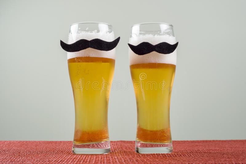 Two glasses with beer and a symbolic mustache. royalty free stock image