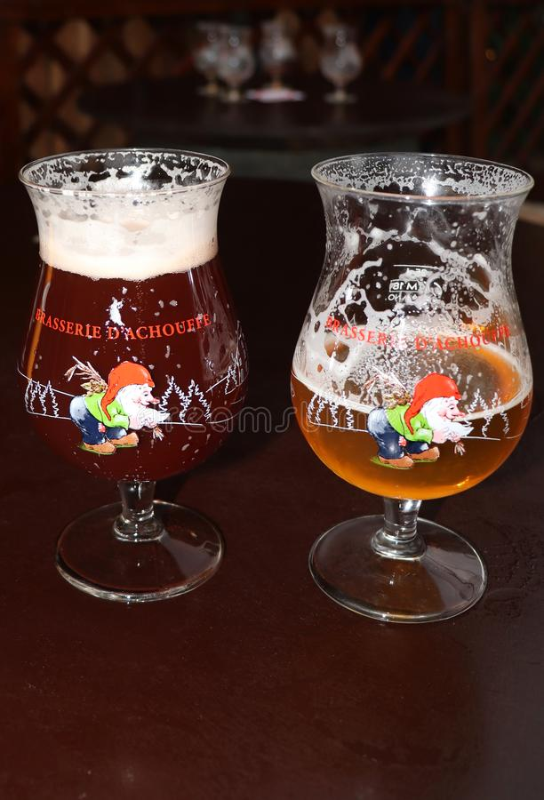 Two glasses of beer on a table in Ghent, Belgium. Two holiday glasses of beer on a table with a table of empty glasses in the background at a Christmas Market in stock photos