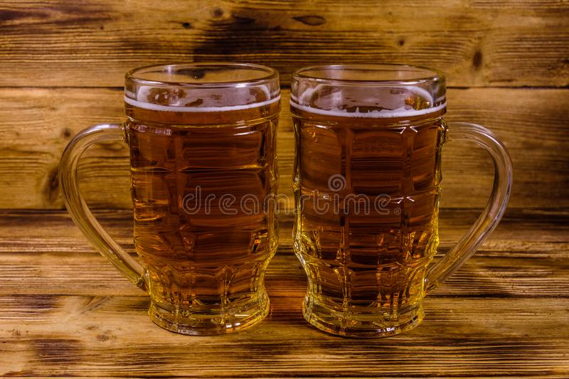 Two glasses of beer on wooden table. Two glasses of beer on rustic wooden table royalty free stock images
