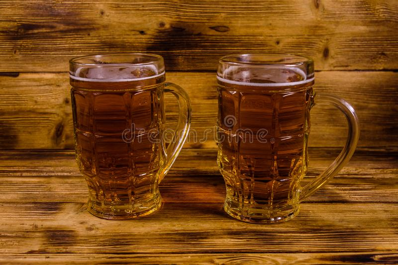 Two glasses of beer on wooden table. Two glasses of beer on rustic wooden table stock photo