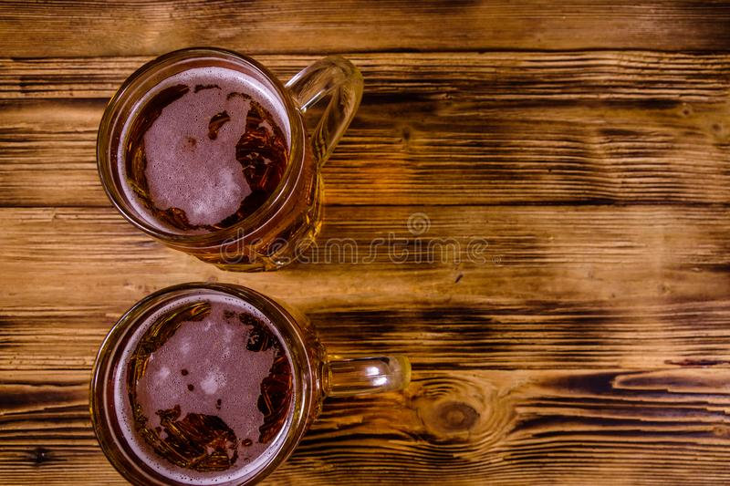 Two glasses of beer on wooden table. Top view. Two glasses of beer on rustic wooden table. Top view stock photos