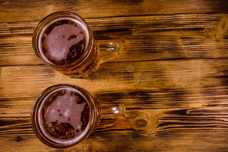 Two glasses of beer on wooden table. Top view. Two glasses of beer on rustic wooden table. Top view royalty free stock photo