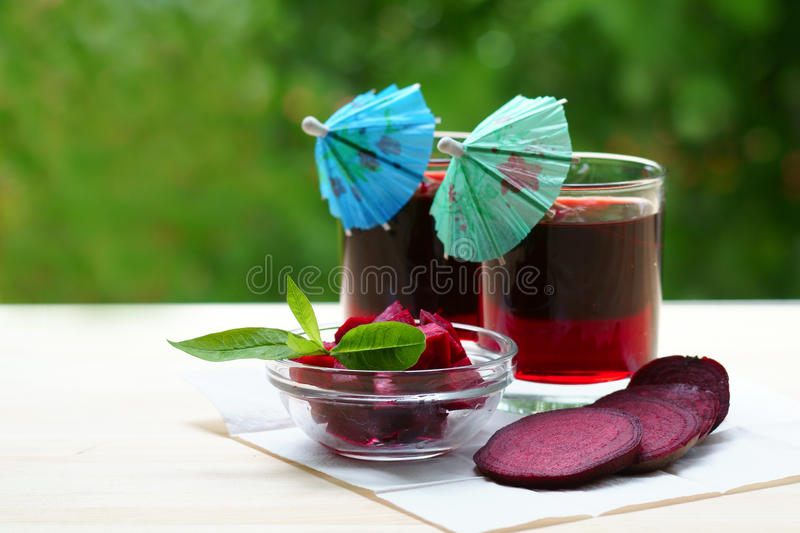Two glasses of beet juice with umbrellas stock image
