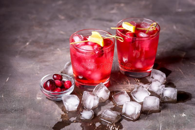 Two Glasses of Berries Cold Drink Tasty Cranberry Lemonade with Ice Dark Photo Black Background Horizontal royalty free stock photo