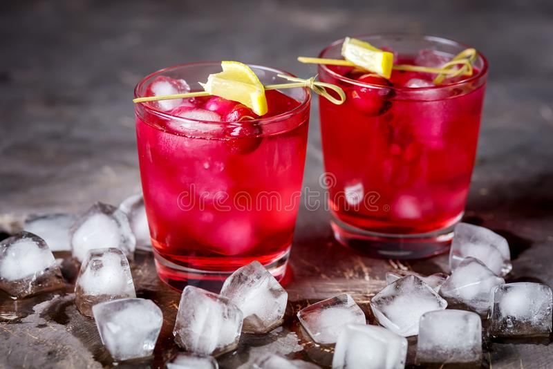 Two Glasses of Berries Cold Drink Tasty Cranberry Lemonade with Ice Dark Photo Black Background Horizontal royalty free stock images
